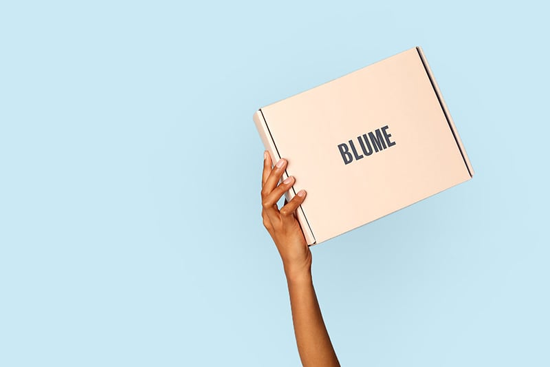 Blume box held up by a hand on a blue background