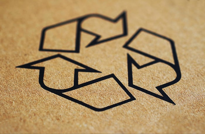 Recycle symbol on a cardboard background