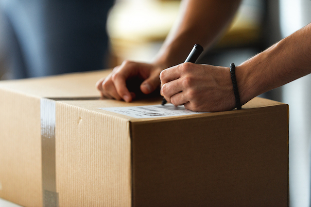 Man writing on a box
