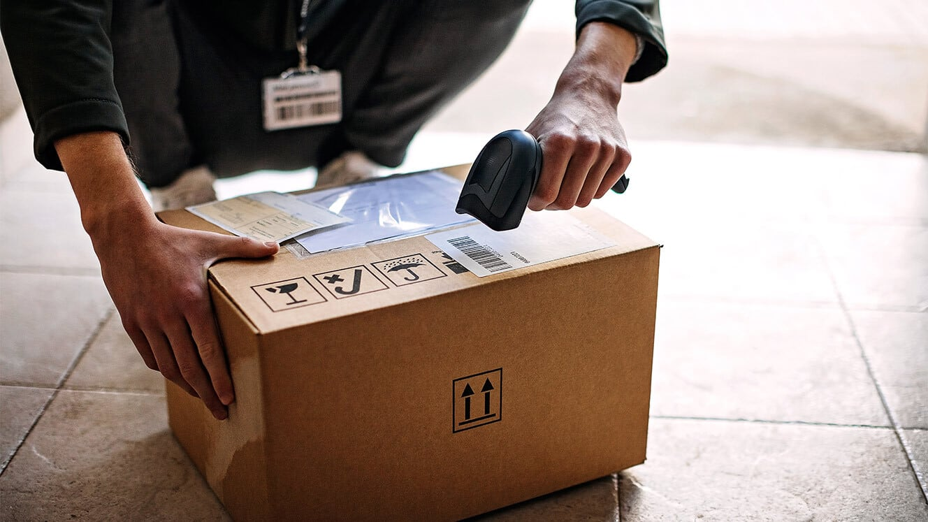 person scanning box on ground
