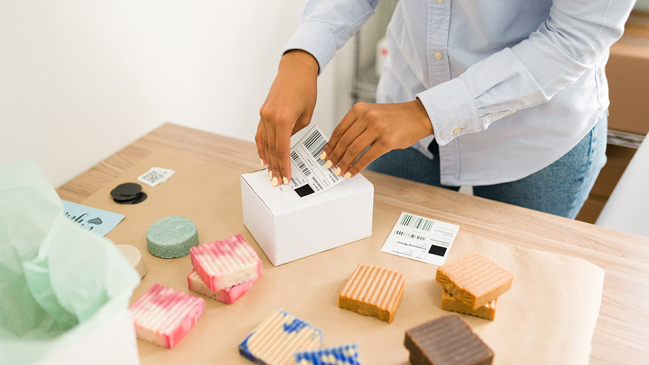 Person packing homemade soaps to ship
