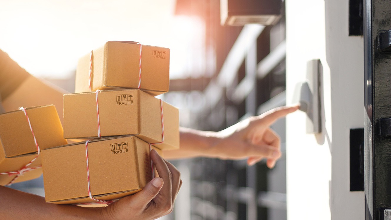 Person holding stack of fragile boxes