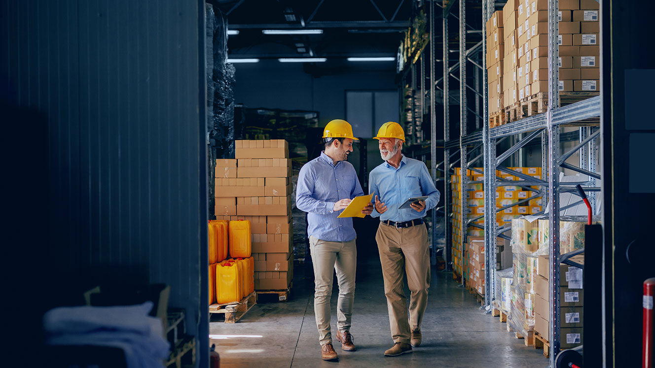 Two People In Hardhats Conversing