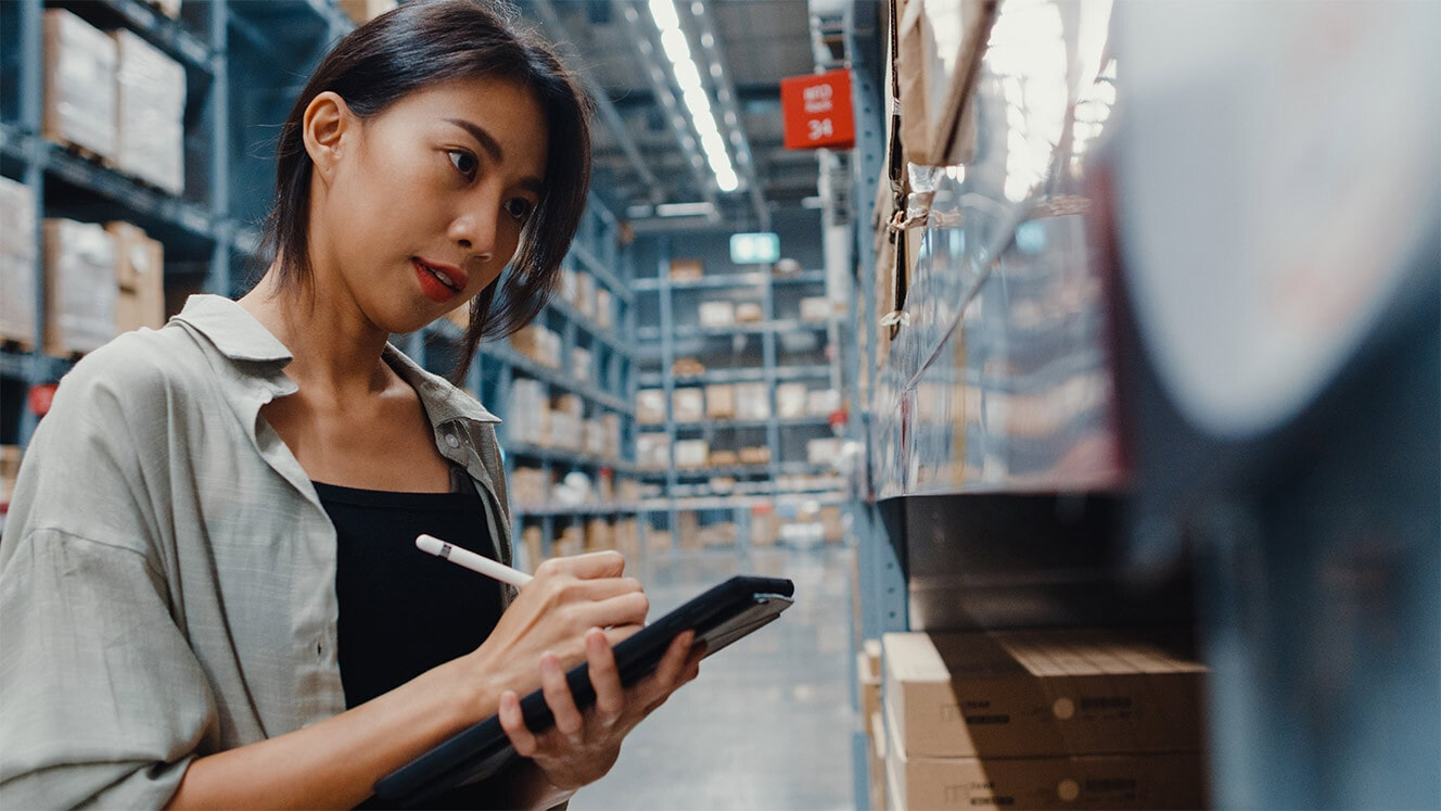 A woman writes on a tablet while looking at items on a shelf in a warehouse